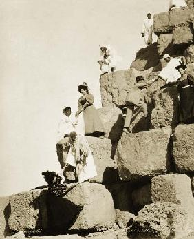 Tourists ascending the pyramids with native guides (b/w photo)