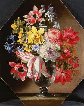 A Glass Vase of Flowers on a Stone Ledge Containing Tulips, Chrysanthemums, Roses and Bluebells