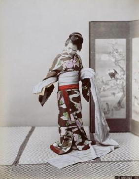 Young Japanese Girl Dressing, late 19th century (hand coloured photo)