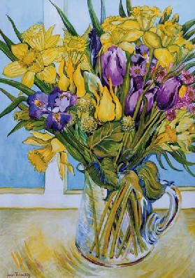 Daffodils and tulips in a glass jug by a window