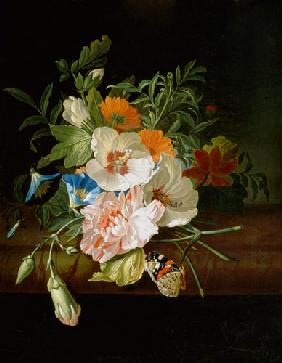 Flower still life with butterflies at a stone bank.