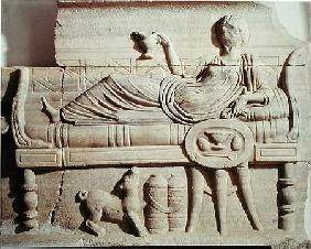 Detail from a sarcophagus depicting a woman reclining on a bench