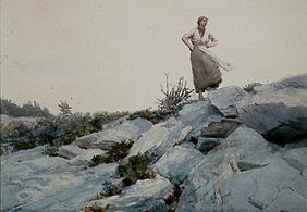 Young woman on rocks standing.
